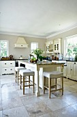 Elegant island counter with white stools on large stone flags in kitchen in French country-house style