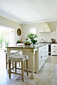 Elegant island counter and white bar stools on large stone flags in kitchen