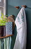 Tea towel printed with fern leaves hung on green wall