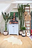 Zimmerpflanzen um ein Schränkchen mit Bild von Frida Kahlo