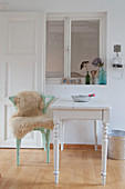 Sheepskin on chair at old table in front of interior window