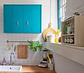 Bright blue kitchen cupboards above sink next to window