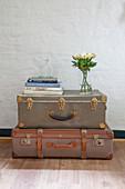 Zwei gestapelte alte Koffer mit Büchern und Blumen
