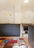 Grey cupboards in minimalist kitchen with vaulted ceiling