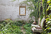 Old sofa in courtyard with Virginia creeper growing over garden wall