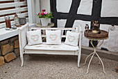 Cushions on shabby-chic bench against half-timbered wall