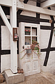 Old wooden door decorated with flowers outside half-timbered house