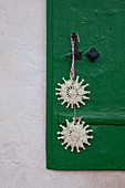 Two straw stars hung on green shutter
