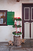 Three Advent wreaths on etagere outside front door of farmhouse