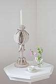 Candlestick made from corrugated cardboard on small white table