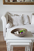 Dish on nest of side tables in front of white sofa with white scatter cushions