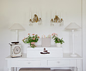 Flowers and ornaments arranged symmetrically on console table