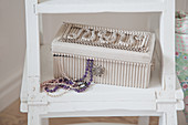 Jewellery box made from corrugated cardboard and bead necklace on ladder