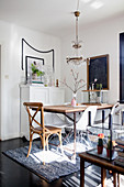 Various chairs at table with metal frame in eclectic dining room