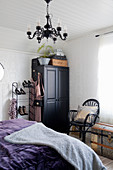 Black wardrobe and chandelier in vintage-style bedroom