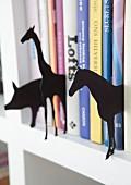 Verschiedene Tier-Silhouetten aus schwarzer Pappe zwischen Büchern
