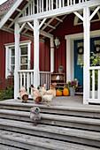 Hühner auf der Treppe zum Eingang eines roten Schwedenhauses
