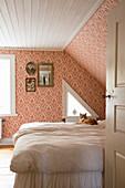 Katze auf dem Bett im nostalgischen Schlafzimmer mit rot gemusterter Tapete