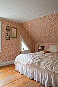 White bed with valance in vintage-style bedroom with sloping ceiling