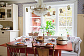 Set red table below window in Scandinavian country-house kitchen