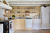 Shelves and yellow wall panelling in country-house kitchen