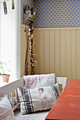Cushions made from old fabrics on bench in rustic kitchen-dining room