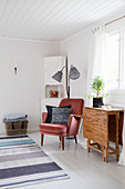 Drop-leaf table and red velvet armchair below window in living room with white floor
