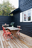 Red spoke-back chairs at wooden table on terrace of black wooden house