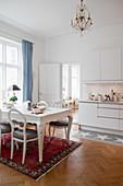 Klassischer Esstisch mit Medaillonstühlen auf Perserteppich und Küchenzeile