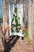 Christmas tree printed on fabric hung between bare trees and little girl wearing white tutu