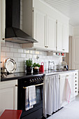 Scandinavian country-house kitchen with white cabinets and classic cooker