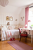 Red upholstered chair and antique desk next to charming in child's bedroom