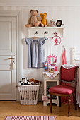 Red upholstered chair in front of coat rack in classic child's bedroom