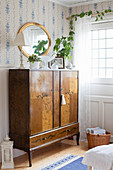 Antique wooden cabinet against blue-and-white wallpaper