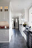 White panelled cabinets and grey floor in large, country-house kitchen
