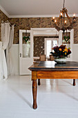 Chandelier above antique wooden table in foyer with white floor