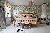 Swedish tiled stove in romantic bedroom with floral wallpaper