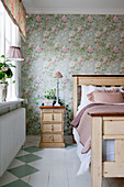 Painted wooden floor and floral wallpaper in romantic bedroom