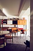 Retro Regalwand mit Schreibtisch, Klassikerstuhl und runder Tisch
