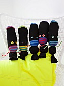 Black hand-made fabric dolls arranged on neon-yellow cushion