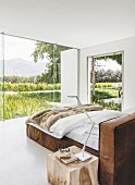 Leather bed in minimalist bedroom with view of landscape