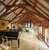 Grand piano in bright room in rustic attic with restored wooden roof structure