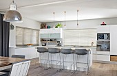 Bar stools at island counter in grey and white modern kitchen