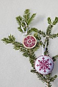 Two hand-made embroidered snowflake decorations on green fir branch