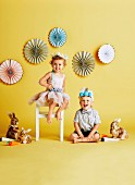Two happy children with tinkered Easter crowns