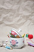 Sewing supplies in old sugar bowl and pin cushion