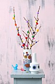 Twigs decorated with colourful pompoms in retro vase