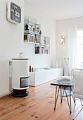 Small cylindrical stove and designer shelves in white living room