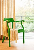 Green retro armchair in front of glass wall with curtain