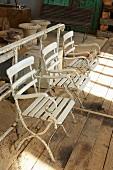 weiße Vintage Gartenstühle auf rustikalem Bretterboden